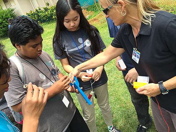 Science teacher Paige Yerxa and students working with a rocket.