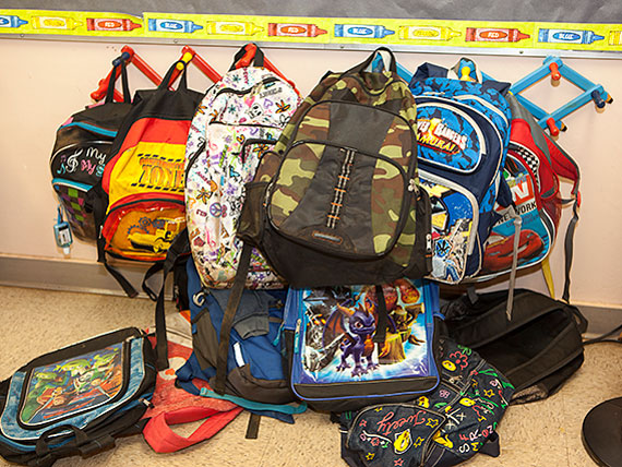 Photo of students' backpacks hanging on a wall during class time.