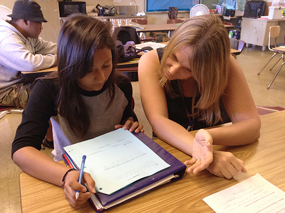 Photo of teacher assisting student with lesson.